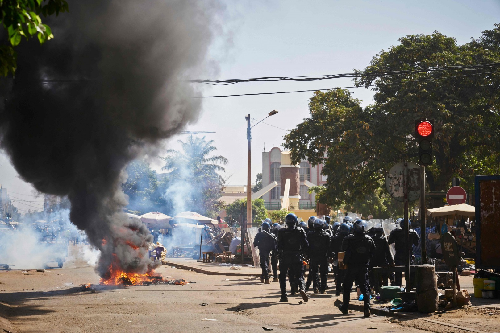 Malian riot police members run past a burning barricade during a protest called by opposition parties in Bamako on December 8, 2018. (Photo by MICHELE CATTANI / AFP)