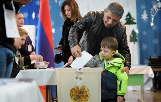 A man casts his ballot with his son as part of early parliamentary elections in Yerevan on December 9, 2018. (Photo by Karen MINASYAN / AFP)