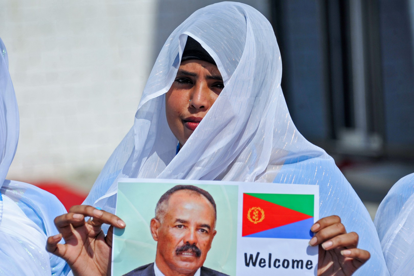 A Somali woman waits for the arrival of Eritrea's President as she holds a picture of him at Aden Abdulle international airport in Mogadishu, on December 13, 2018 ahead of his meeting with his Somalian counterpart. (Photo by Mohamed ABDIWAHAB / AFP)
