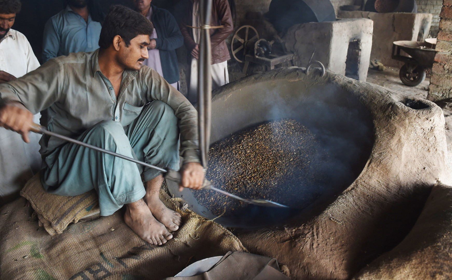 A Pakistani vendor roasts pine nuts at a market in Lahore on December 13, 2018. - Pakistan is among the world top pine nut producers. (Photo by ARIF ALI / AFP)