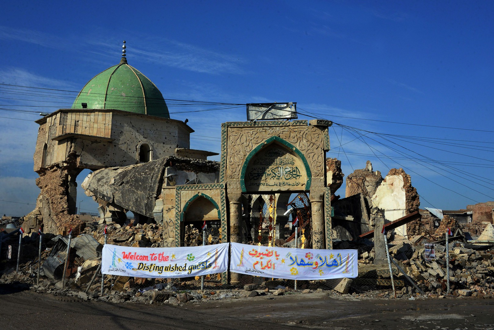 """A picture taken on December 16, 2018, shows the Great Mosque of al-Nuri and """"Al-Hadba"""" leaning minaret in Mosulís war-ravaged Old City, during the placing of the corner stone ceremony. - The famed 12th century mosque and minaret, dubbed Al-Hadba or """"the hunchback,"""" were where IS chief Abu Bakr al-Baghdadi made his only public appearance to declare a self-styled """"caliphate"""" after sweeping into Mosul in 2014. The structures were ravaged three years later in the final, most brutal stages of the months-long fight against IS. (Photo by Zaid AL-OBEIDI / AFP)"""