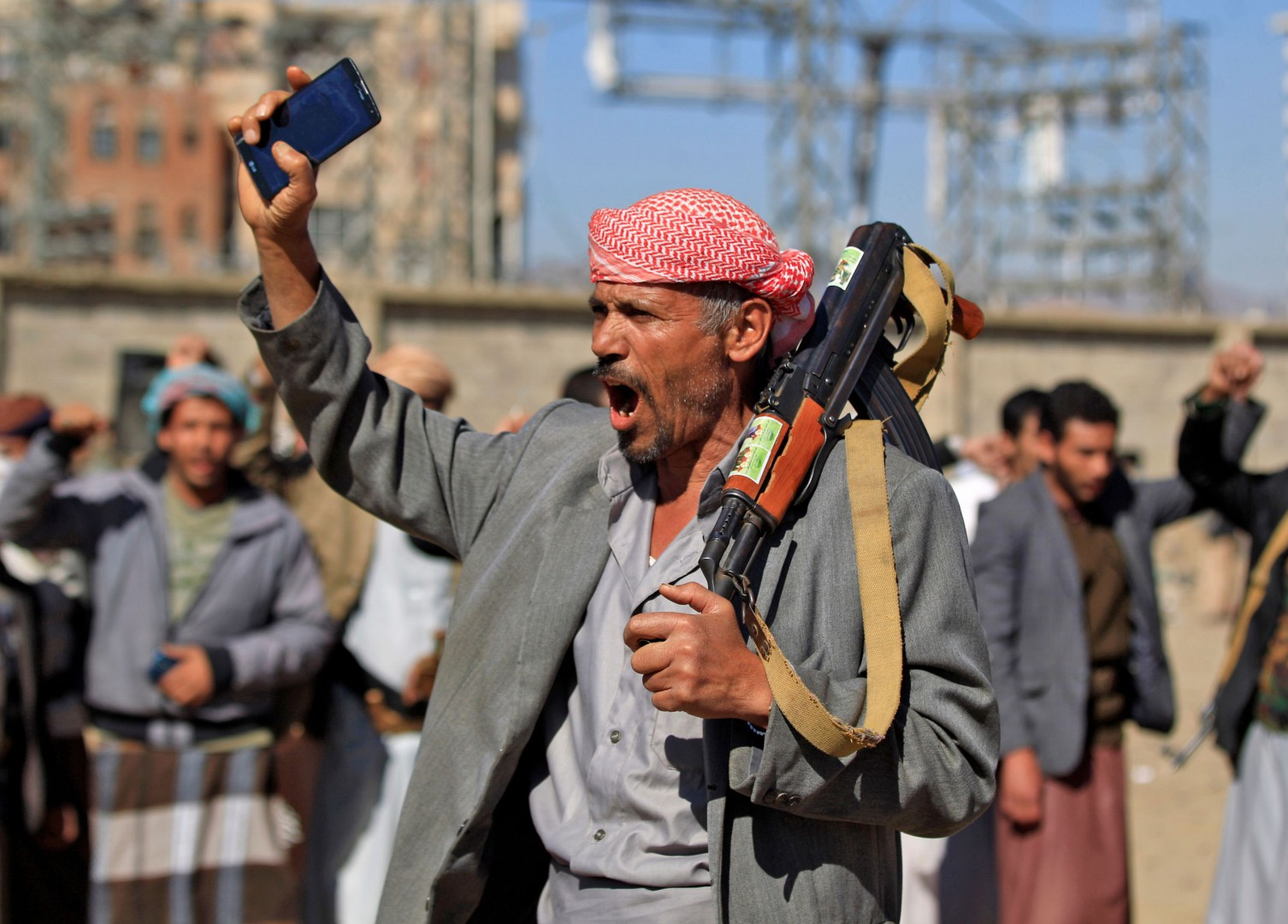 An Yemeni man holds an AK-47 as people gather in the capital Sanaa to show their support to the Shiite Huthi movement against the Saudi-led intervention, on December 19, 2018. - A hard-won truce in the battleground Yemeni city of Hodeida will collapse if rebel violations persist and the United Nations does not intervene, the Saudi-led coalition said on December 19. UN observers are due in Yemen to head up monitoring teams made up of government and rebel representatives tasked with overseeing the implementation of the UN-brokered ceasefire that took effect on Tuesday. (Photo by Mohammed HUWAIS / AFP)