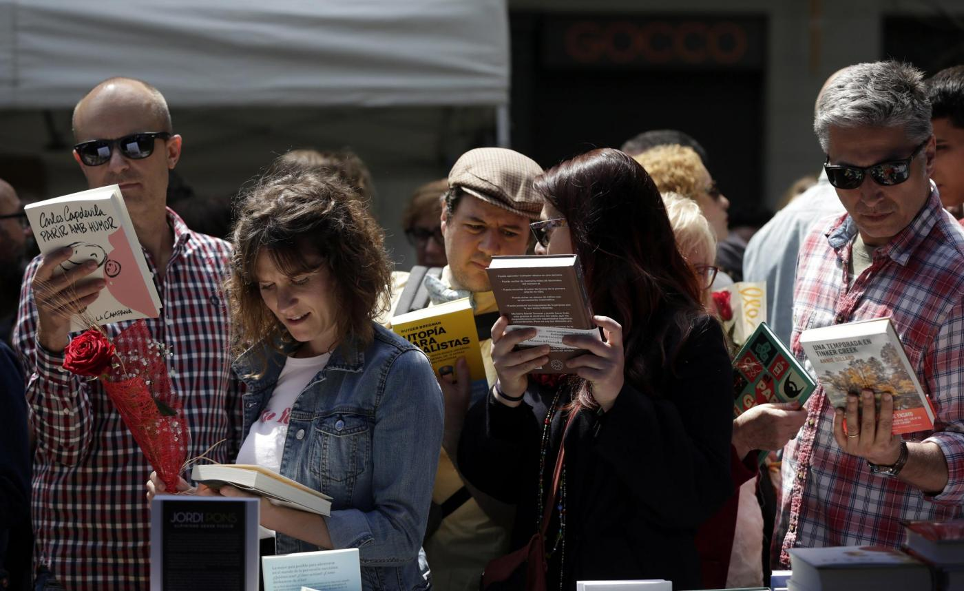 People search for books in a street stall on the occasion of Saint Jordi feast, in downtown Barcelona, northeastern Spain, on 23 April 2017. Books and roses are the main gifts citizens give each other in order to celebrate this day that also features hundreds of cultural, musical, gastronomic and solidarity activities. EFE/Alberto Estevez