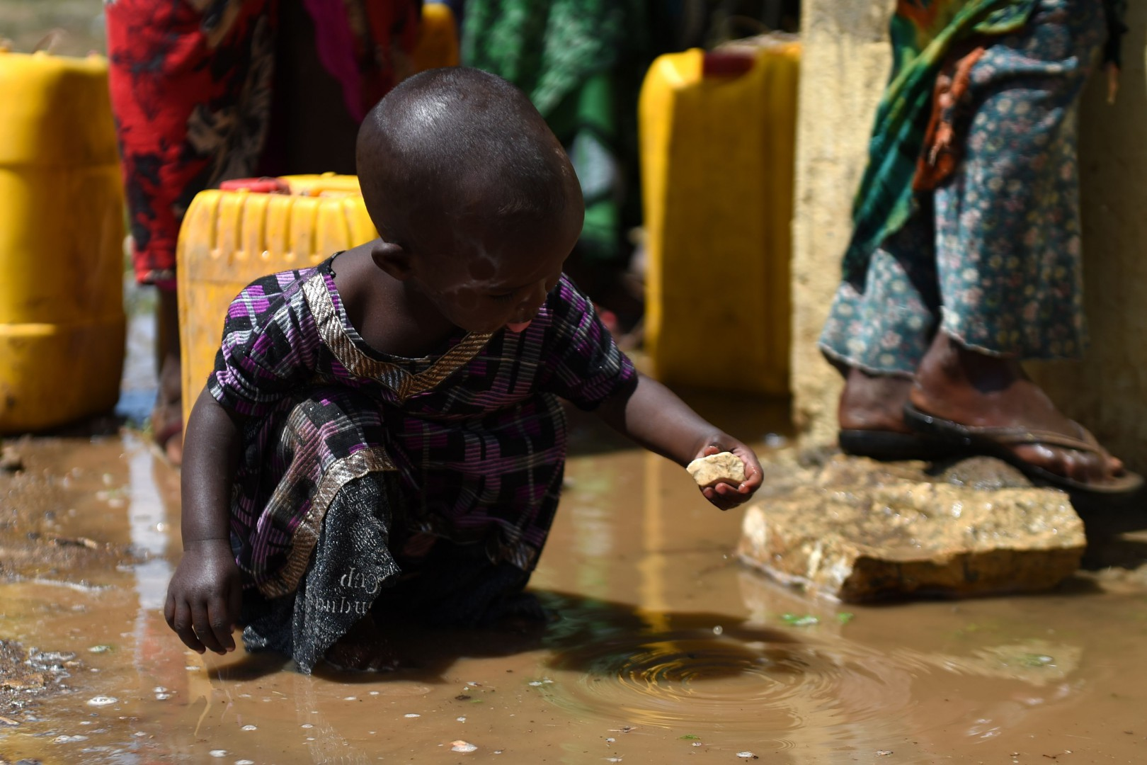 A young girl plays with a stone in a puddle of water in the village of Afraaga, Somaliland where charity CARE International have built a storage tank and installed pipelines and taps to give villagers access to clean water from a nearby borehole. PRESS ASSOCIATION Photo. Picture date: Friday May 12, 2017. Villagers across the self-proclaimed state of Somaliland are suffering drought and are on the verge of famine after a lack of rainfall in recent years. See PA story CHARITY Famine. Photo credit should read: Joe Giddens/PA Wire