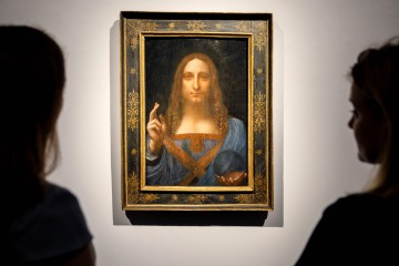"""(FILES) In this file photo taken on October 24, 2017 Christie's employees pose in front of a painting entitled Salvator Mundi by Italian polymath Leonardo da Vinci at a photocall at Christie's auction house in central London. The Louvre Abu Dhabi said on June 27, 2018 it will unveil its most prized acquisition to date, a Leonardo da Vinci painting that sold for nearly half a billion dollars at auction, on September 18. The 500-year-old """"Salvator Mundi"""" painting depicting Jesus Christ, believed to be the work of the Renaissance master's own hand, set a new art auction record when it sold for $450.3 million in November 2017.  / AFP PHOTO / Tolga Akmen / RESTRICTED TO EDITORIAL USE - MANDATORY MENTION OF THE ARTIST UPON PUBLICATION - TO ILLUSTRATE THE EVENT AS SPECIFIED IN THE CAPTION"""