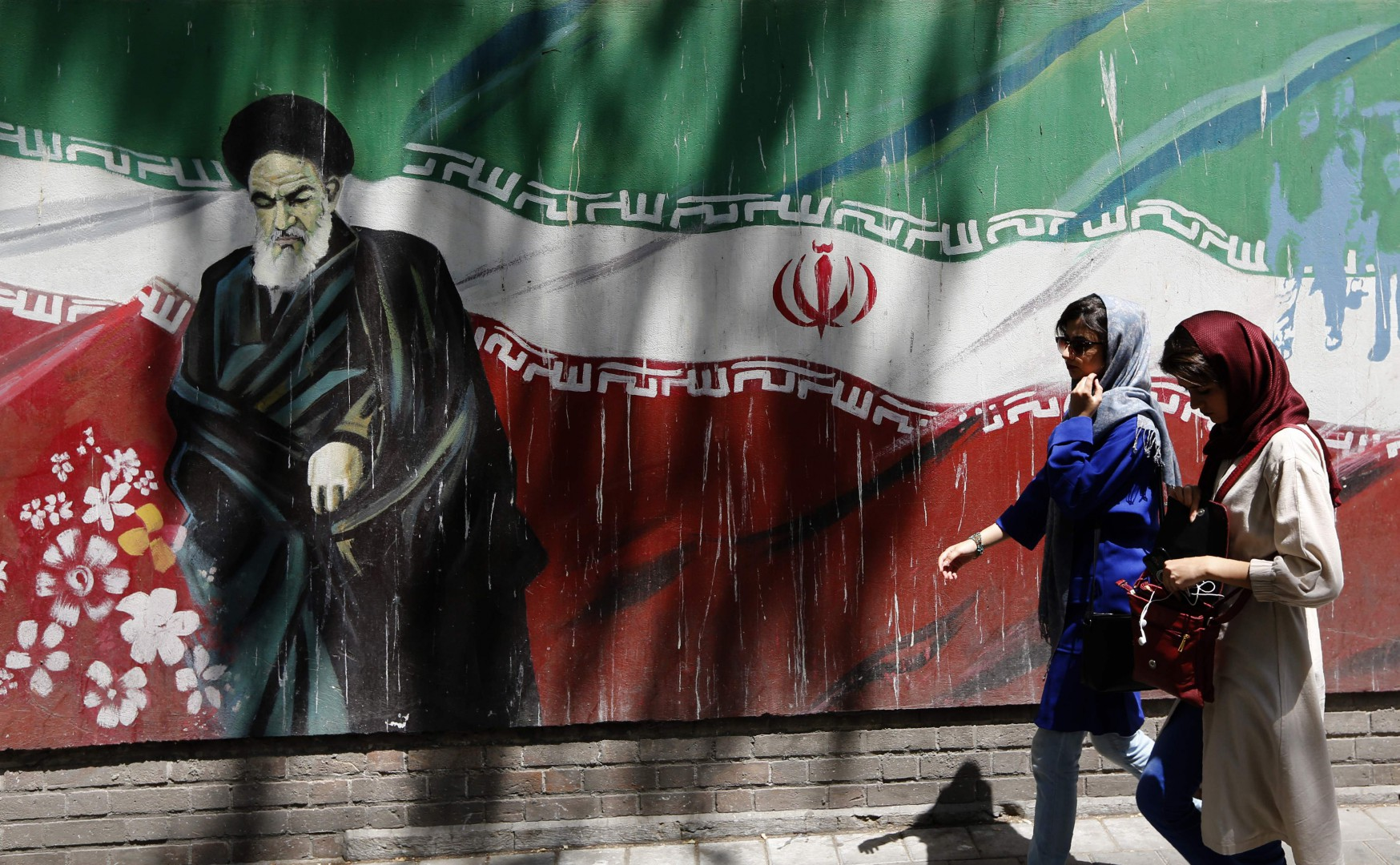 "Iranians walk by mural painting of the founder of the Islamic Republic Ayatollah Ruhollah Khomeini on the wall of the former US embassy in the Iranian capital Tehran on August 7, 2018. US President Donald Trump warned countries against doing business with Iran today as he hailed the ""most biting sanctions ever imposed"", triggering a mix of anger, fear and defiance in Tehran. / AFP PHOTO / ATTA KENARE"