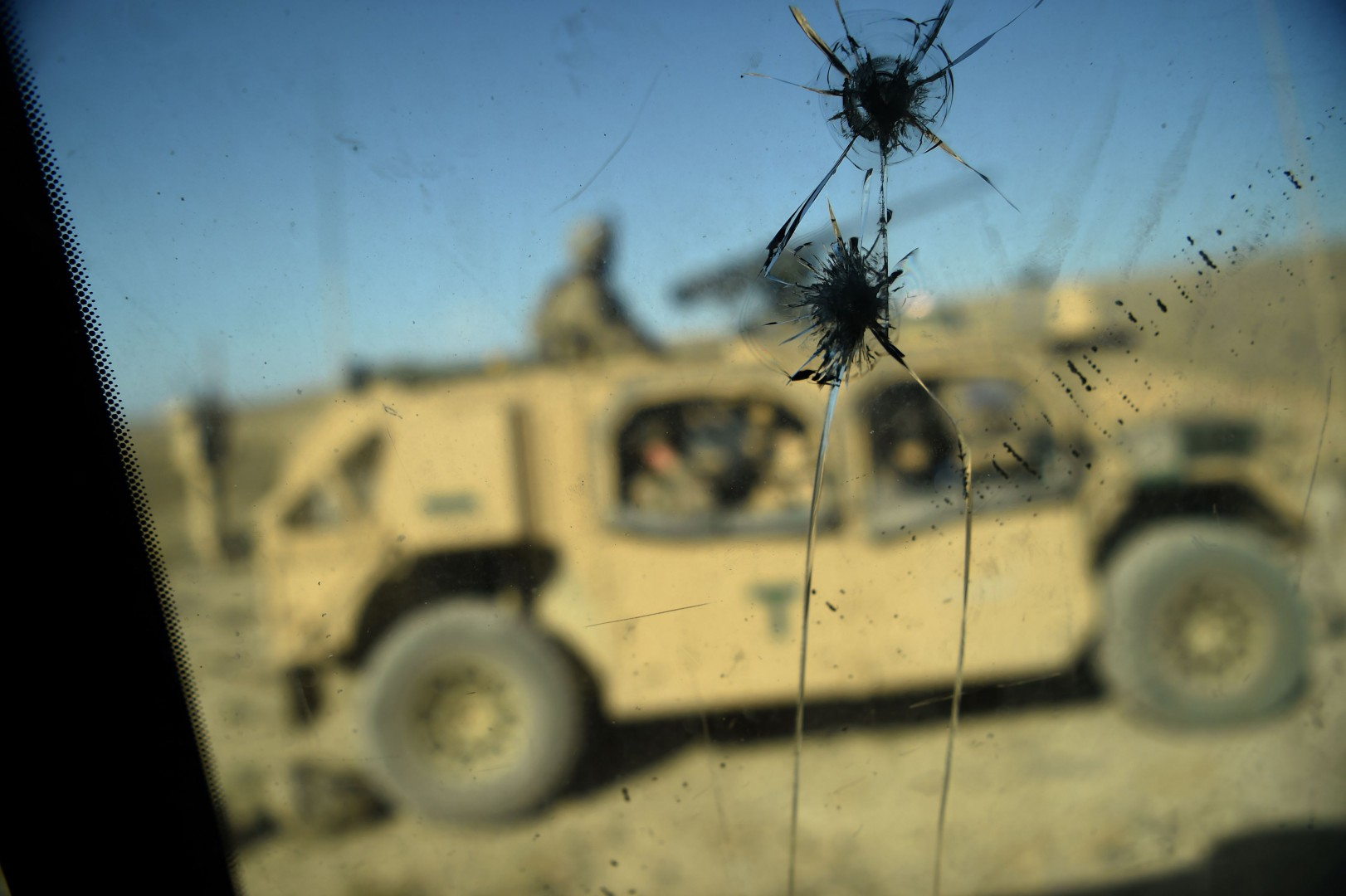 (FILES) In this file photo taken on July 07, 2018 US Army soldiers from NATO are seen through a cracked window of an armed vehicle in a checkpoint during a patrol against Islamic State militants at the Deh Bala district in the eastern province of Nangarhar Province. - The Afghan conflict could overtake Syria as the deadliest conflict in the world this year, analysts say, as violence surges 17 years after the US-led invasion. (Photo by WAKIL KOHSAR / AFP)