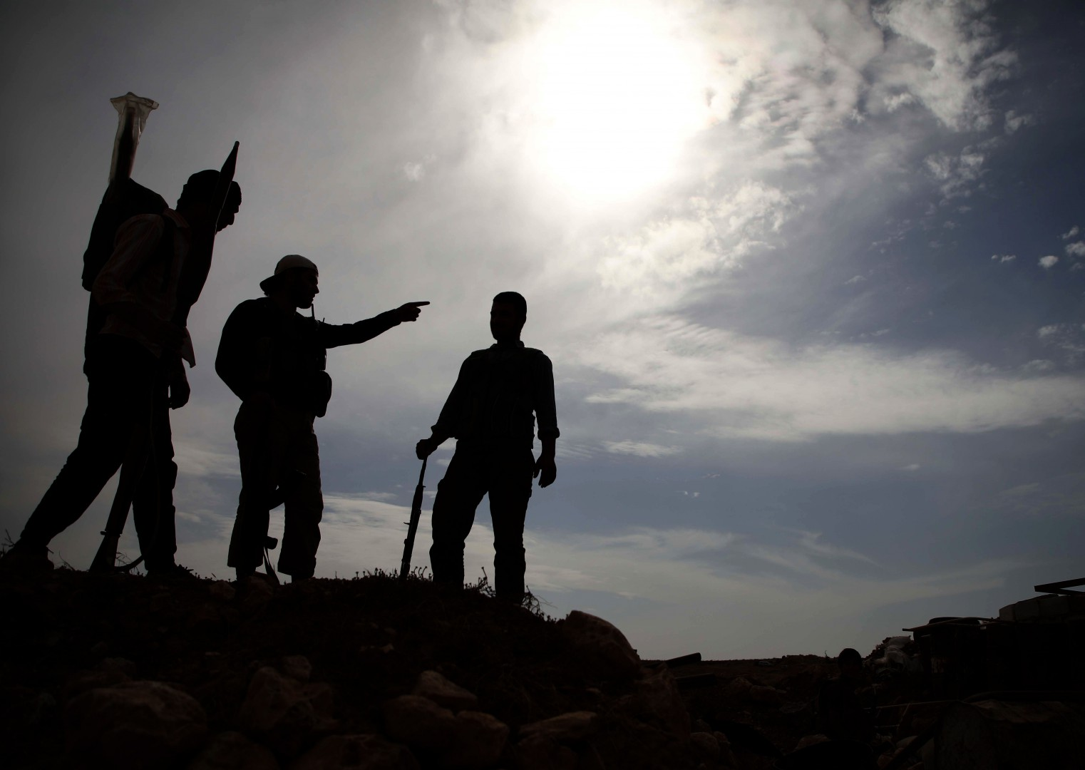 TOPSHOT - Syrian rebel-fighters with the National Liberation Front (NLF) stand on a hill overlooking regime-held areas in northwestern countryside of Aleppo province on October 9, 2018. - Jihadists and Turkish-backed rebels in Syria's last major opposition stronghold have withdrawn heavy weapons from nearly all of a planned buffer zone, a monitor said today, a day ahead of deadline. (Photo by Aaref WATAD / AFP)
