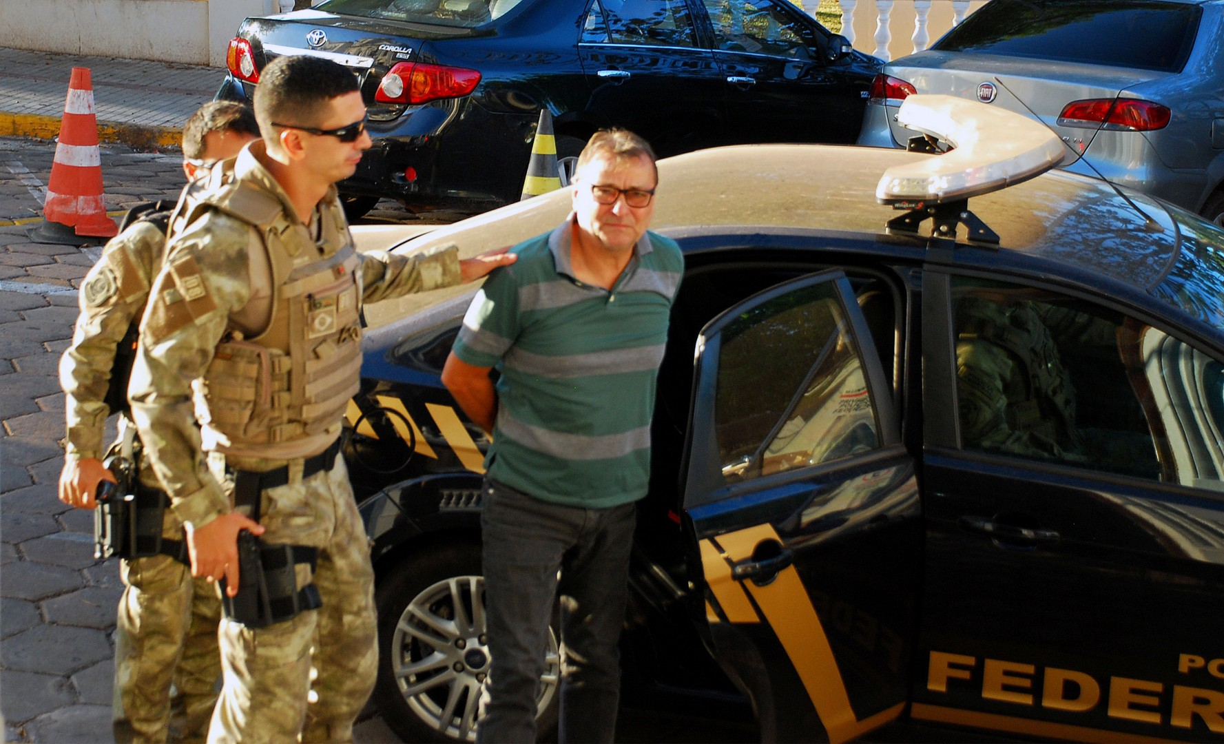 "(FILES) In this file photo taken on October 05, 2017 Italian ultra-leftist militant Cesare Battisti arrives escorted by police to the headquarters of the Federal Police in Corumba, Mato Grosso do Sul State, West of Brazil, after a federal judge ordered his preventive detention. - Brazil's far-right presidential frontrunner Jair Bolsonaro said on October 16, 2018 that, if he won, he would extradite ""the terrorist"" Cesare Battisti, an Italian wanted in his homeland for four murders attributed to a far-left extremist group in the 1970s. (Photo by FABIO MARCHI / AFP)"