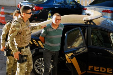 """(FILES) In this file photo taken on October 05, 2017 Italian ultra-leftist militant Cesare Battisti arrives escorted by police to the headquarters of the Federal Police in Corumba, Mato Grosso do Sul State, West of Brazil, after a federal judge ordered his preventive detention. - Brazil's far-right presidential frontrunner Jair Bolsonaro said on October 16, 2018 that, if he won, he would extradite """"the terrorist"""" Cesare Battisti, an Italian wanted in his homeland for four murders attributed to a far-left extremist group in the 1970s. (Photo by FABIO MARCHI / AFP)"""