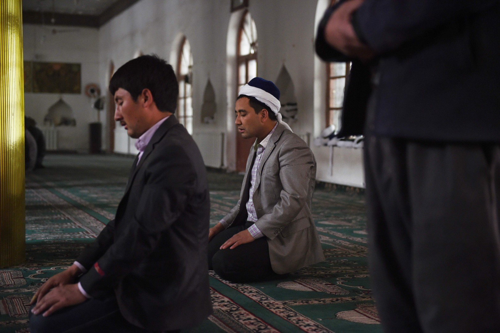 "This photo taken on April 16, 2015 shows Uighur men praying in a mosque in Hotan, in China's western Xinjiang region. - The prefecture in the region's south has seen an explosion in the construction of ìvocational training"" centres for the region's Muslim minorities. But the centres have come under international scrutiny, with rights activists describing them as political re-education camps holding as many as one million ethnic Uighurs and other Muslim minorities. (Photo by Greg Baker / AFP) / TO GO WITH China-politics-rights-Xinjiang, FOCUS by Ben Dooley"