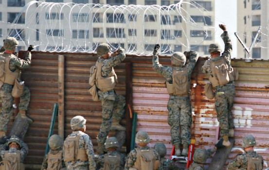 US marines put barbed wire atop fencing along the United States-Mexico border in San Ysidro, California, on November 9, 2018. (Photo by Sandy Huffaker / AFP)