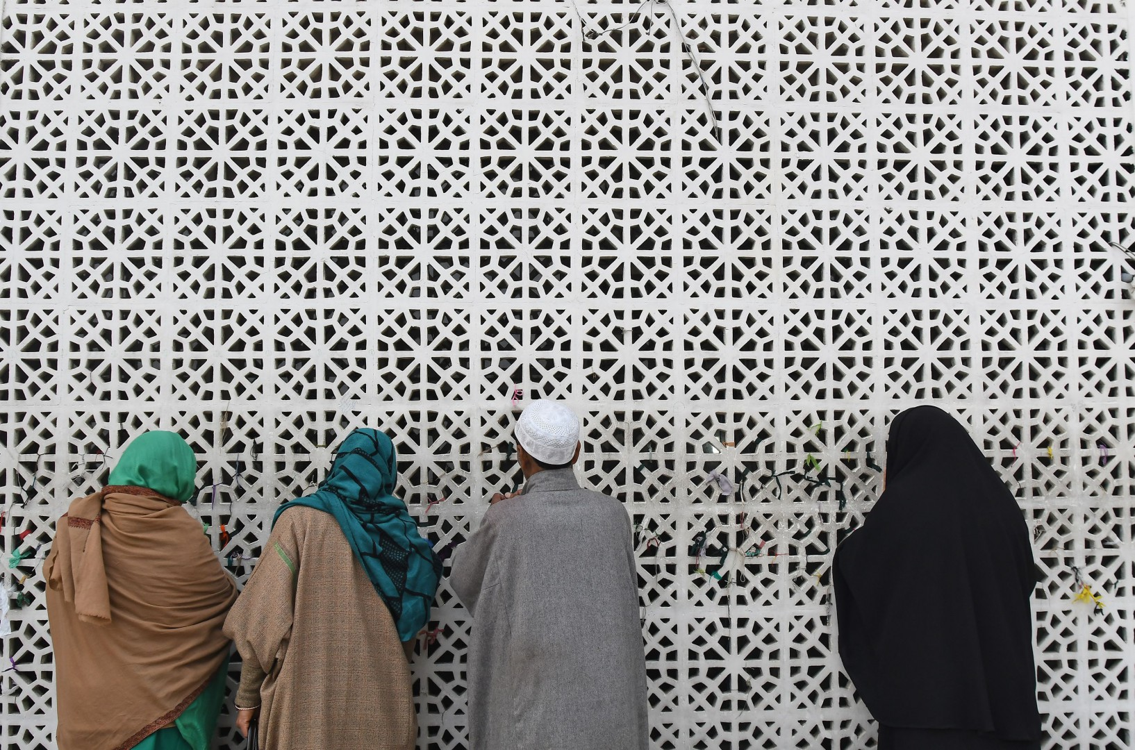 Kashmiri Muslims pray at a wall at Hazratbal Shrine before the presentation of a holy relic, believed to be a hair from the beard of Prophet Muhammad, during Eid Milad-un-Nabi, the birthday of the Prophet, at the Hazratbal Shrine in Srinagar on November 21, 2018. - Thousands of Kashmiri Muslims gathered at the shrine in the summer capital of Jammu and Kashmir to offer prayers on the Prophet's birth anniversary. (Photo by TAUSEEF MUSTAFA / AFP)