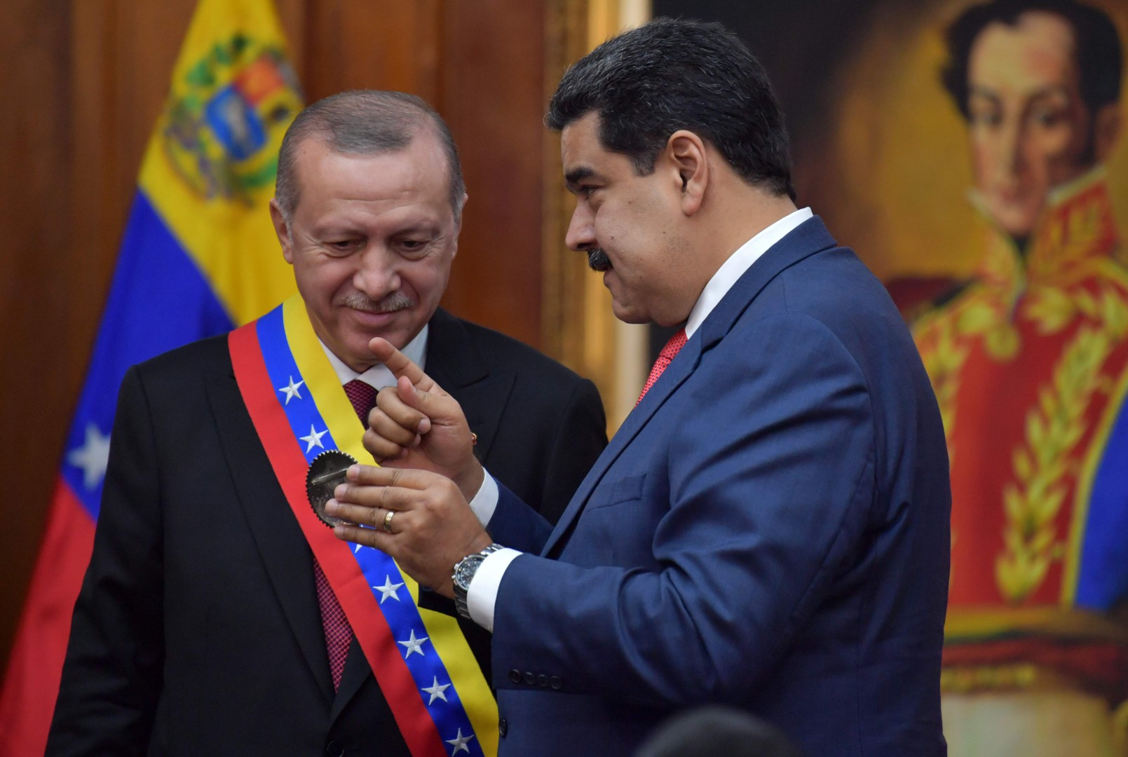 Venezuelan President Nicolas Maduro (R) decorates Turkish President Recep Tayyip Erdogan with the Order of the Liberator during a meeting at Miraflores Presidential Palace in Caracas, on December 3, 2018. (Photo by Yuri CORTEZ / AFP)