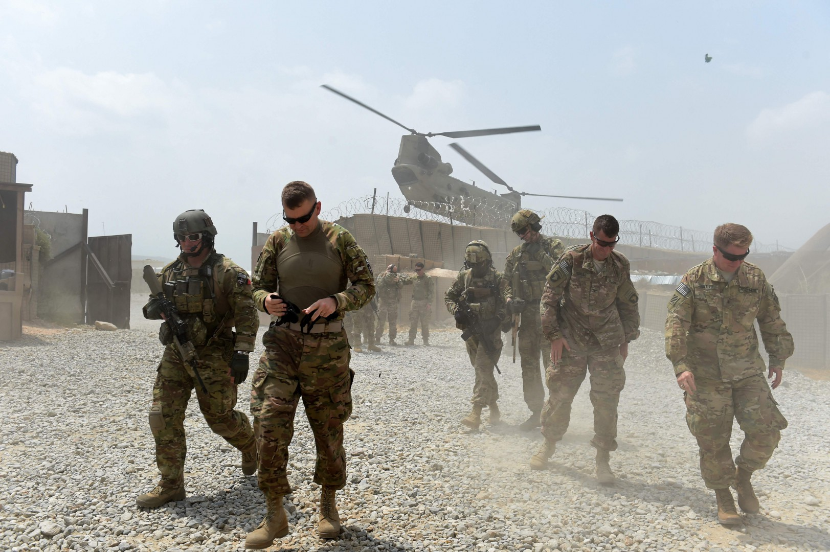 "(FILES) In this file photo taken on August 12, 2015 US army soldiers walk as a NATO helicopter flies overhead at coalition force Forward Operating Base (FOB) Connelly in the Khogyani district in the eastern province of Nangarhar. - President Donald Trump has decided to pull a significant number of troops from Afghanistan, a US official told AFP on Thursday, a day after he announced a withdrawal from Syria. ""That decision has been made. There will be a significant withdrawal,"" the official told AFP on condition of anonymity. (Photo by Wakil KOHSAR / AFP)"