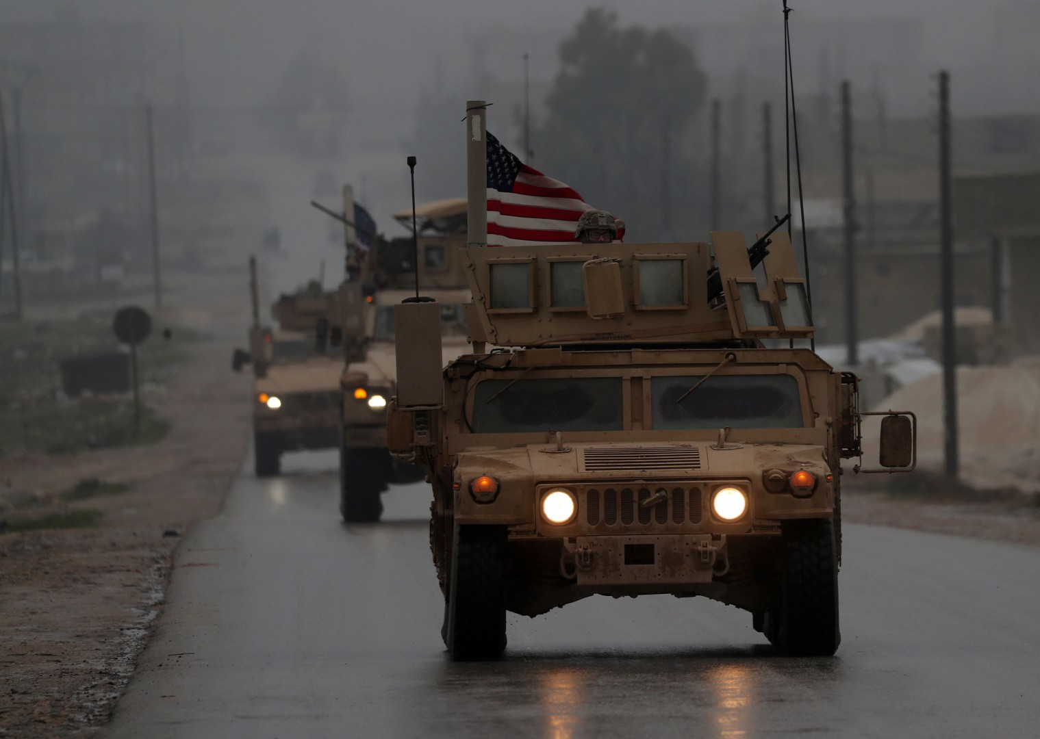 """(FILES) In this file photo taken on December 30, 2018, shows a line of US military vehicles in Syria's northern city of Manbij. - President Donald Trump appeared to backtrack on December 31, 2018 on shock plans for an immediate pullout of US troops from Syria, but said his drive to end American involvement in wars made him a """"hero."""" The shift came a day after a senior Republican senator said Trump had promised to stay in Syria to finish the job of defeating the Islamic State group, also known as ISIS. (Photo by Delil SOULEIMAN / AFP)"""