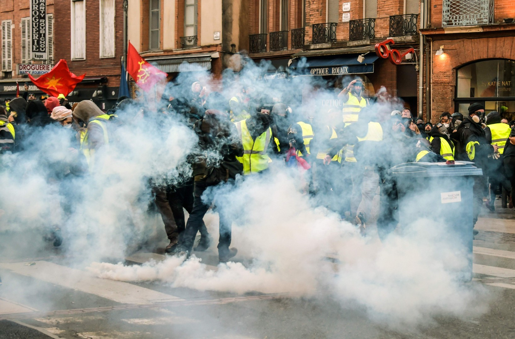 "Protesters stand in tear gas as they clash with riot police on January 5, 2019  in Toulouse, during a demonstration called by the yellow vests (gilets jaunes) movement for the eighth week in a row of nationwide protest against high cost of living, government tax reforms and for more ""social and economic justice."" (Photo by PASCAL PAVANI / AFP)"