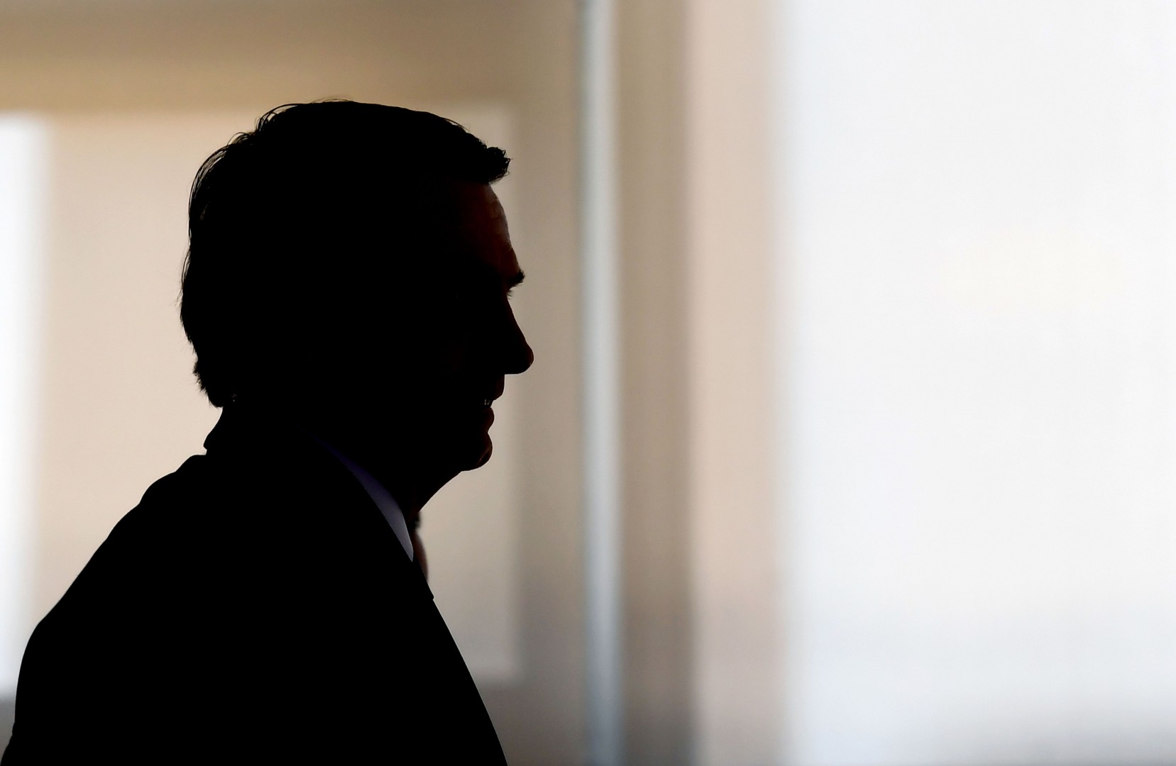 TOPSHOT - Brazilian President Jair Bolsonaro is silhouetted during the appointment ceremony of the new heads of public banks, at Planalto Palace in Brasilia on January 7, 2019. - Brazil's Finance Minister Paulo Guedes appointed the new presidents of the country's public banks. (Photo by EVARISTO SA / AFP)