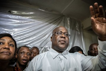 """Felix Tshisekedi gestures as he is surrounded by his wife, relatives and supporters of his UDPS party (Union for Democracy and Social Progress), a few minutes after he was declared winner of the presidential election following the announcement of the provisional results by the Independent National Electoral Commission (CENI), in his father's historic residence in Limete, Kinshasa on January 10, 2019. - France on January 10, 2019 challenged the outcome of DR Congo's presidential election, saying the declared victory of opposition chief Felix Tshisekedi was """"not consistent"""" with the results and that his rival Martin Fayulu appeared to have won. (Photo by Caroline Thirion / AFP)"""