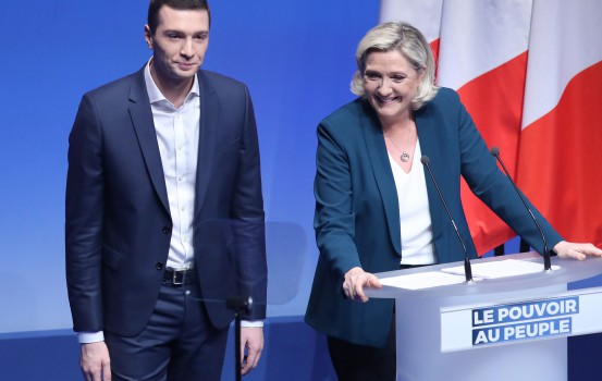 President of the French far-right Rassemblement National (RN) party Marine Le Pen (R) smiles flanked by RN spokeman Jordan Bardella  on January 13, 2019, in Paris, during a meeting to launch the RN's campaign for the European elections of May 2019. (Photo by JACQUES DEMARTHON / AFP)