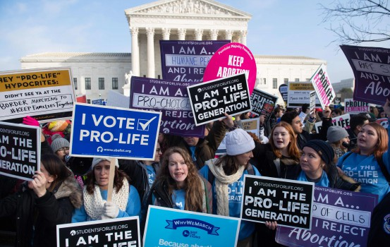 """Pro-choice activists hold signs in response to anti-abortion activists participating in the """"March for Life,"""" an annual event to mark the anniversary of the 1973 Supreme Court case Roe v. Wade, which legalized abortion in the US, outside the US Supreme Court in Washington, DC, January 18, 2019. (Photo by SAUL LOEB / AFP)"""