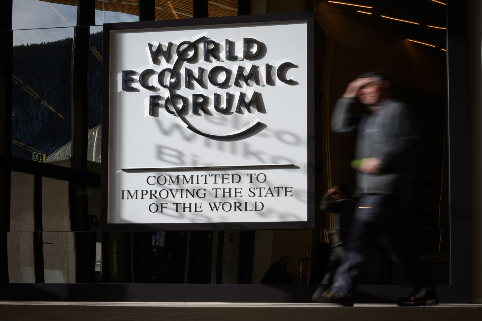 A staff walks past a sign ahead of the opening of the 2019 World Economic Forum (WEF) annual meeting on January 20, 2019 in Davos, eastern Switzerland. (Photo by Fabrice COFFRINI / AFP)