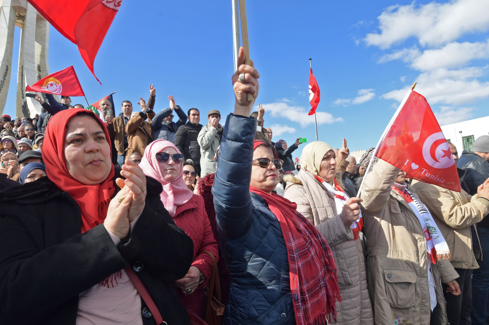 Tunisian teachers shout slogans, wave national flags, and raise protest signs during a demonstration demanding wage increases outside the Prime Minister's office in the capital Tunis on February 6, 2019. (Photo by FETHI BELAID / AFP)