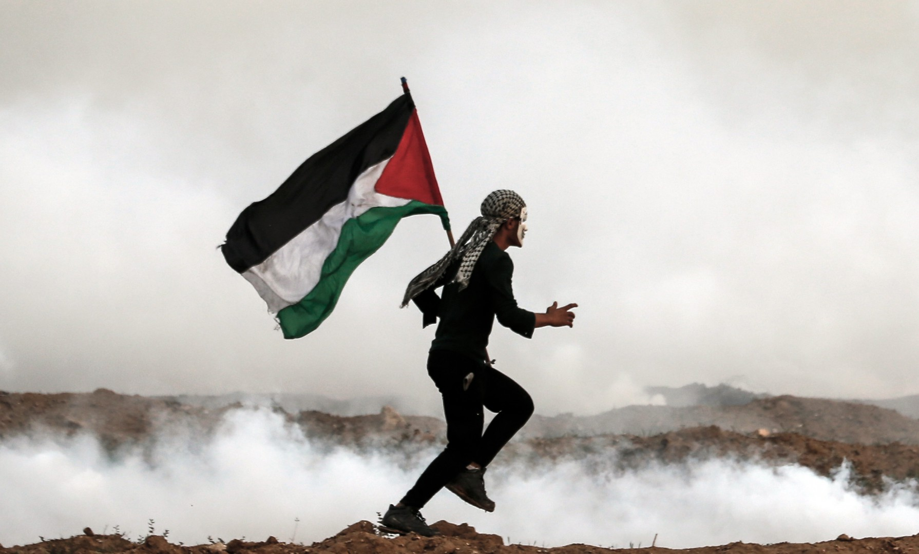 A Palestinian man holds the national flag as he runs through teargas during a protest on November 16, 2018, on the eastern outskirts of Gaza City, near the border with Israel. (Photo by MAHMUD HAMS / AFP)