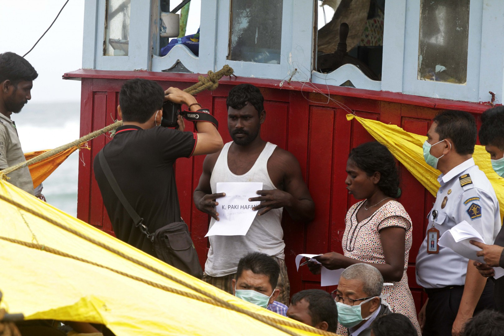 (160617) -- ACEH, June 17, 2016 (Xinhua) -- An Indonesian immigration officer takes a photo of a Sri Lankan for identification on a migrant boat stranded at Lhoknga Beach, Aceh, Indonesia, June 16, 2016. About 44 migrants onboard from Sri Lanka drifted into Aceh waters after an engine failure. According to the Indonesian Immigration Office, the migrants were heading to Australia when the engine problem occurred. (Xinhua/Junaidi) ****Authorized by ytfs****