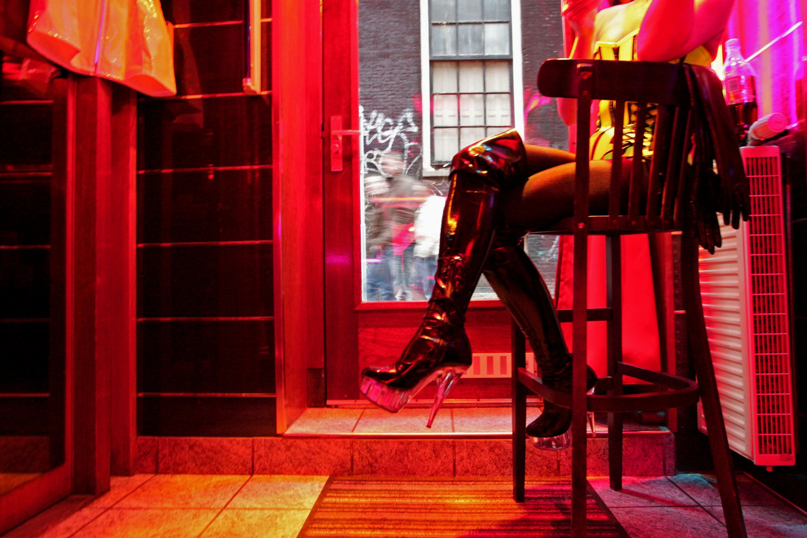 "(FILES) This file photo taken on December 6, 2008 shows a prostitute, waiting for clients behind her window in the red light district of Amsterdam.  From behind their glass walls, at the bends of dark corridors and dark rooms, sex workers have not waited for the arrival of the world's best science and medicine to become aware of the risk they face by practising the ""oldest profession of the world"". Emblematic of the Dutch city of Amsterdam, these dens of prostitution come out of the shadows this week while the city hosts the International AIDS Conference from July 23 until July 27, 2018. ""When we chose Amsterdam to host the conference, it was with the idea of highlighting the people that are the most vulnerable and exposed to HIV,"" says Linda-Gail Bekker, President of the International AIDS Society (IAS). / AFP PHOTO / ANOEK DE GROOT"