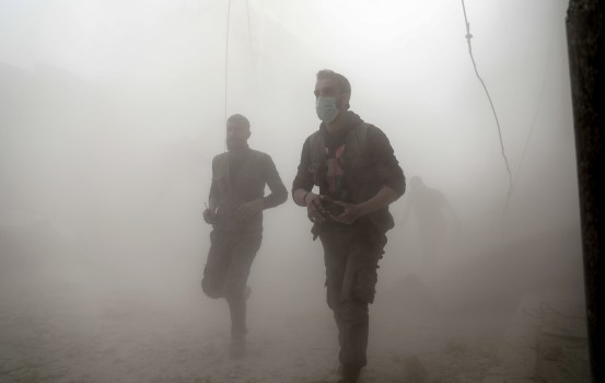 (FILES) In this file photo taken on February 25, 2017 Syrian Civil Defence volunteers, also known as the White Helmets, run amid the smoke and dust in search for survivors following reported government airstrike on the rebel-held town of Douma, on the eastern outskirts of the capital Damascus. Jordan said on July 22, 2018 that it has taken in 800 Syrian White Helmets rescuers who had been evacuated by Israel from Syria as they were threatened by advancing regime forces in the south of the war-ravaged country. Jordan plans to transfer them to the United Kingdom, Canada, and Germany. Founded in 2013, the Syria Civil Defence, or White Helmets, are a network of first responders who rescue wounded in the aftermath of air strikes, shelling or blasts in rebel-held territory. / AFP PHOTO / Sameer Al-Doumy
