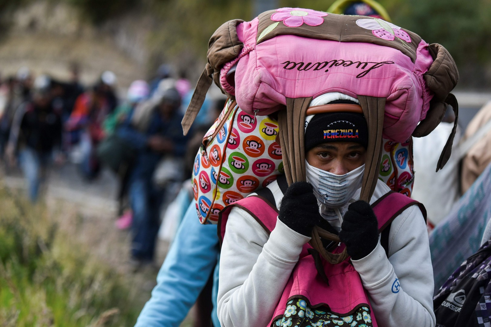 TOPSHOT - A Venezuelan migrant woman heading to Peru carries bags as she walks along the Panamerican highway in Tulcan, Ecuador, after crossing from Colombia, on August 21, 2018. - Ecuador announced on August 16 that Venezuelans entering the country would need to show passports from August 18 onwards, a document many are not carrying. And Peru followed suit on August 17, announcing an identical measure due to begin on August 25. (Photo by Luis ROBAYO / AFP)