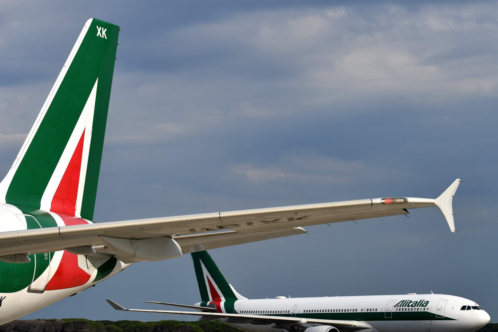 (FILES) In this file photo taken on June 21, 2018 two Alitalia airplanes are seen rolling on the tarmac at the Fiumicino Airport, in Rome. - Troubled Italian carrier Alitalia has received three takeover offers as part of its latest rescue efforts, the company said in a statement on October 31, 2018. The offers will be examined by Alitalia's external administrators before being passed on to Italy's ministry of economic development. (Photo by Alberto PIZZOLI / AFP)