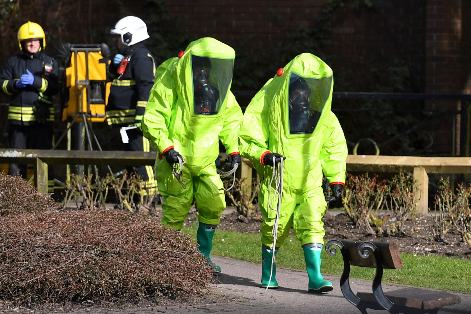 """(FILES) In this file photo taken on March 08, 2018 Members of the fire brigade in green biohazard encapsulated suits work to re-attach the tent over the bench where a man and a woman were found in critical condition sparking a major incident on March 4 at The Maltings shopping centre in Salisbury, southern England, on March 8, 2018 after the tent became detached. - The head of the MI6 foreign spy agency warned Russia on December 3, 2018 not to underestimate Britain's capabilities and determination to expose malign behaviour, ahead of a rare public speech. Alex Younger, who as head of the intelligence agency is known as """"C"""", will use the speech to highlight adversaries who regard themselves as being in perpetual confrontation with Britain. (Photo by Ben STANSALL / AFP)"""
