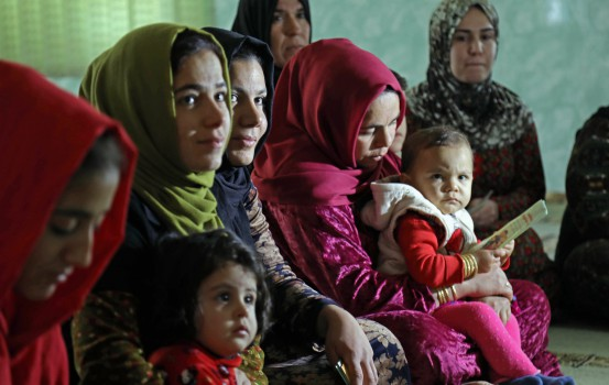 Women and young girls listen to Rasul (not pictured), an Iraqi Kurdish activist with the non-profit organisation WADI, as she peaks about the harms of genital mutilation in Sharboty Saghira, a small village east of regional capital Arbil, on December 3, 2018. - Female genital mutilation appears to have been practiced for decades in Iraq's Kurdish region, usually known for more progressive stances on women's rights. Victims are usually between four and five years old but are impacted for years by bleeding, extremely reduced sexual sensitivity, tearing during childbirth, and depression. (Photo by SAFIN HAMED / AFP)