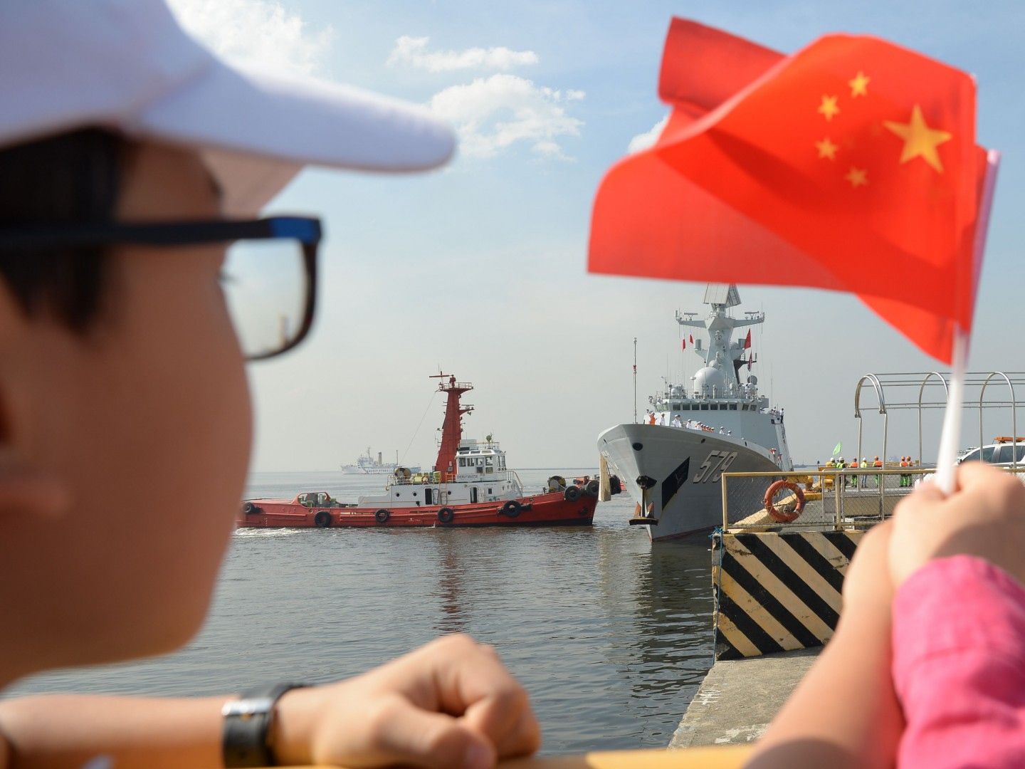 A boy waves a Chinese flag as China's guided-missile frigate Handan (579) prepares to dock at the international port in Manila on January 17, 2019. - A Chinese naval task group, consisting of two frigates -- the Wuhu 539 and Handan 579 -- and a replenishment ship Dongpinghu (960) arrived at Manila's international port for a four-day goodwill visit. (Photo by TED ALJIBE / AFP)