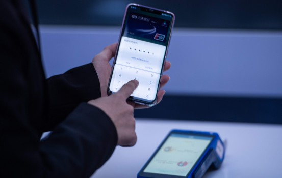 A hostess displays how to use the new Huawei smarthone pay service during a press conference and launch of new 5G Huawei products at the Huawei Beijing Executive Briefing Centre in Beijing on January 24, 2019. (Photo by FRED DUFOUR / AFP)