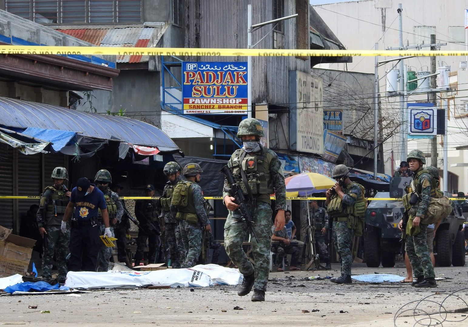 Policemen and soldiers keep watch as body bags (in white), containing the remains of blast victims, as seen in a cordoned area outside a church in Jolo, Sulu province on the southern island of Mindanao, on January 27, 2019. - At least 18 people were killed when two bombs hit a church on a southern Philippine island that is a stronghold of Islamist militants, the military said on January 27, days after voters backed the creation of a new Muslim autonomous region. (Photo by NICKEE BUTLANGAN / AFP)