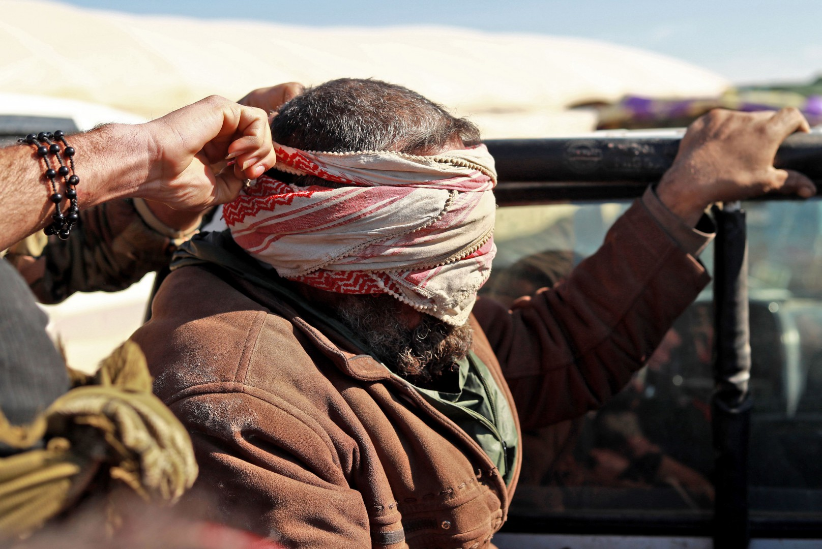 An Alleged Islamic State (IS) group fighters fled from the frontline Syrian village of Baghouz, near the Iraqi border, sits blindfolded in the back of a pickup truck after he was taken into custody by SDF forces for screening, near the Omar oil field in the countryside of the eastern Syrian Deir Ezzor province on January 30, 2019. (Photo by Delil SOULEIMAN / AFP)