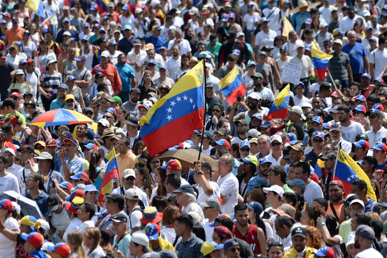 """(FILES) In this file photo taken on February 02, 2019 An opposition supporter waves a national flag during a gathering with Venezuelan opposition leader Juan Guaido, in Caracas on February 2, 2019. - President Donald Trump reiterated in comments broadcast February 3, 2019 that a US military intervention in Venezuela was """"an option,"""" as international pressure ramps up on embattled head of state Nicolas Maduro to step down. Asked in an interview with CBS's """"Face the Nation"""" what could lead the United States to use military force in the crisis-wracked country, the president declined to give a specific answer.""""But certainly it's something that's on the -- it's an option,"""" he said. The United States recognized Venezuelan opposition leader Juan Guaido as interim president on January 23, and is leading an international campaign to drive Maduro from office. (Photo by Federico PARRA / AFP)"""