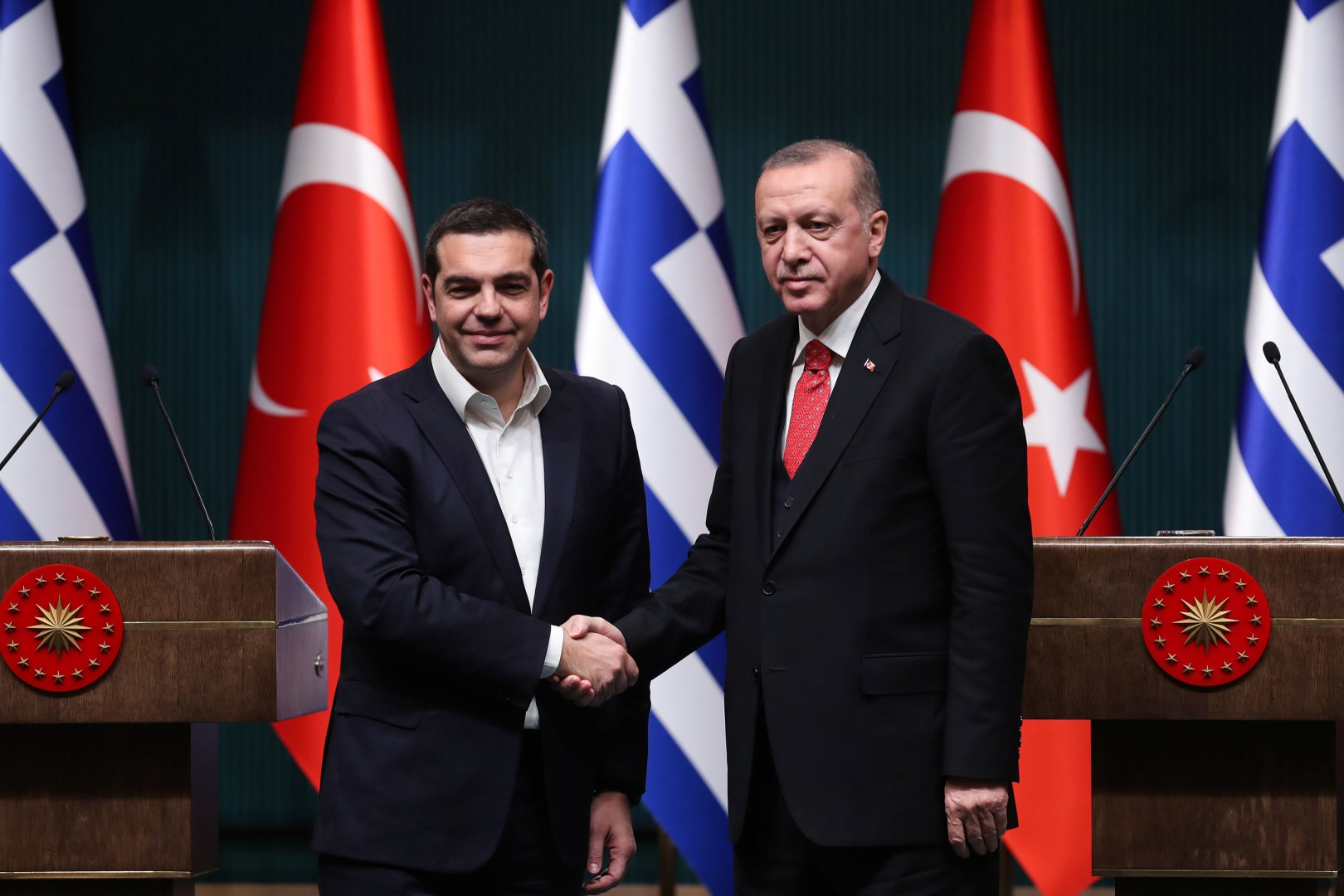 Turkish President Recep Tayyip Erdogan (R) and Greek Prime Minister Alexis Tsipras (L) shake hands at the end of a joint press conference following a meeting at the Presidential Complex in Ankara, on February 5, 2019. (Photo by Adem ALTAN / AFP)