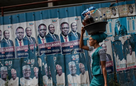 TOPSHOT - A woman with a large plastic bucket filled with drinks and food on her head passes by a wall covered with posters of presidential candidate Atiku Abubakar of the Peoples Democratic Party (PDP,) the official opposition party, in Lagos on February 11, 2019. - Nigerians will participate in the national elections on February 16 where current President Mohammadu Buhari is seeking re-election for the Nigerian ruling party All Prgressives Congress (APC). (Photo by STEFAN HEUNIS / AFP)