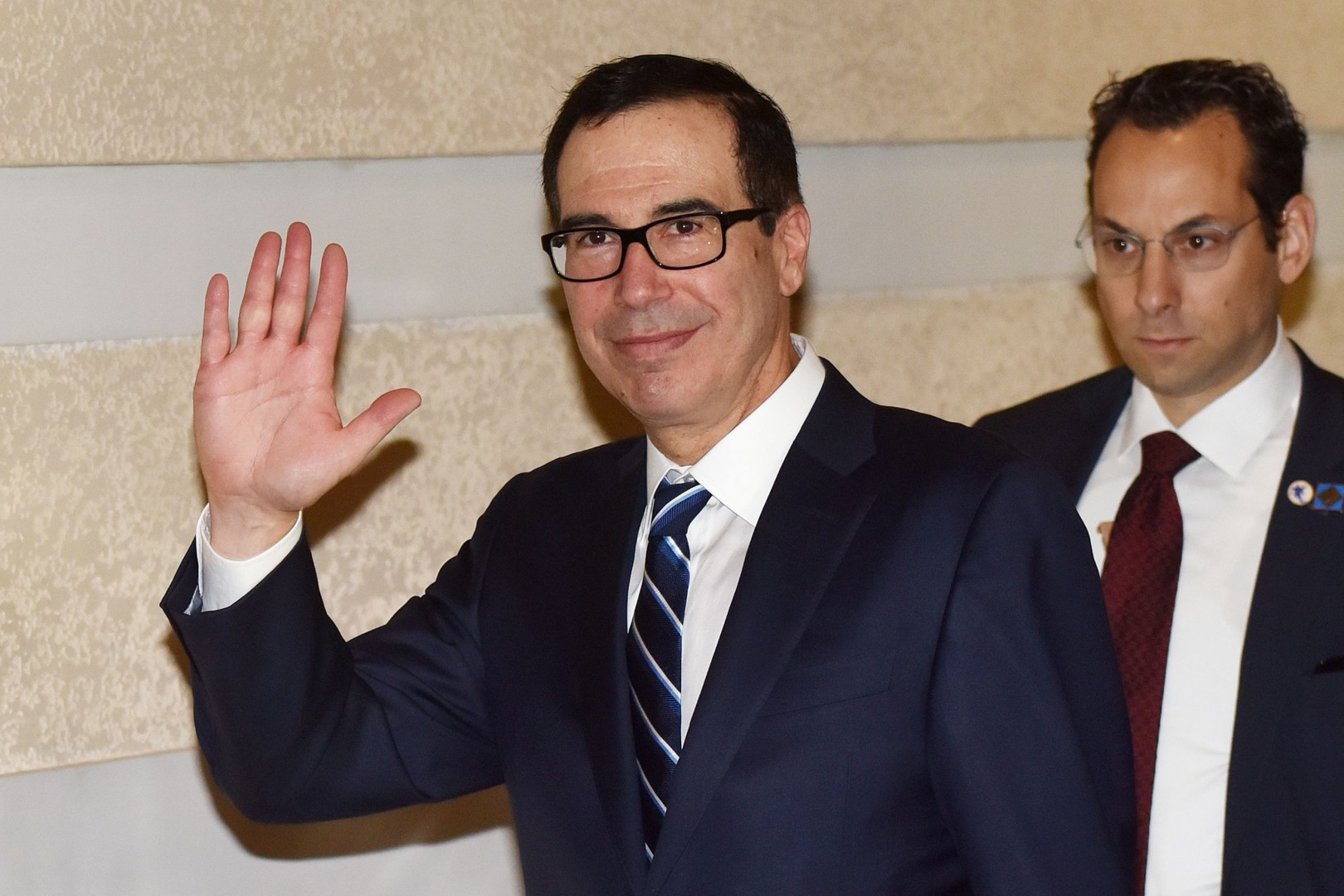 US Treasury Secretary Steven Mnuchin (L) waves as he leaves a hotel with members of a negotiation team in Beijing on February 13, 2019. - Mnuchin will be joined by US Trade Representative Robert Lighthizer as well as David Malpass, President Donald Trump's nominee to lead the World Bank, in negotiations with China set for February 14 and 15. (Photo by Greg Baker / AFP)