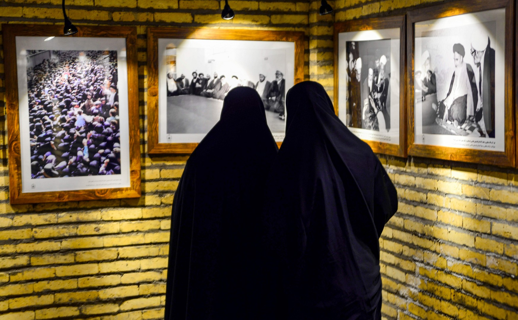 TOPSHOT - Iranian women look at portraits of Islamic Revolution leader Ayatollah Ruhollah Khomeini, as they visit the house where he lived during his 13-year-exile in Iraq, along al-Rasul street near the shrine of Imam Ali in the central holy city of Najaf on February 13, 2019, while marking the 40th anniversary of the Islamic Revolution in Iran. (Photo by Haidar HAMDANI / AFP)