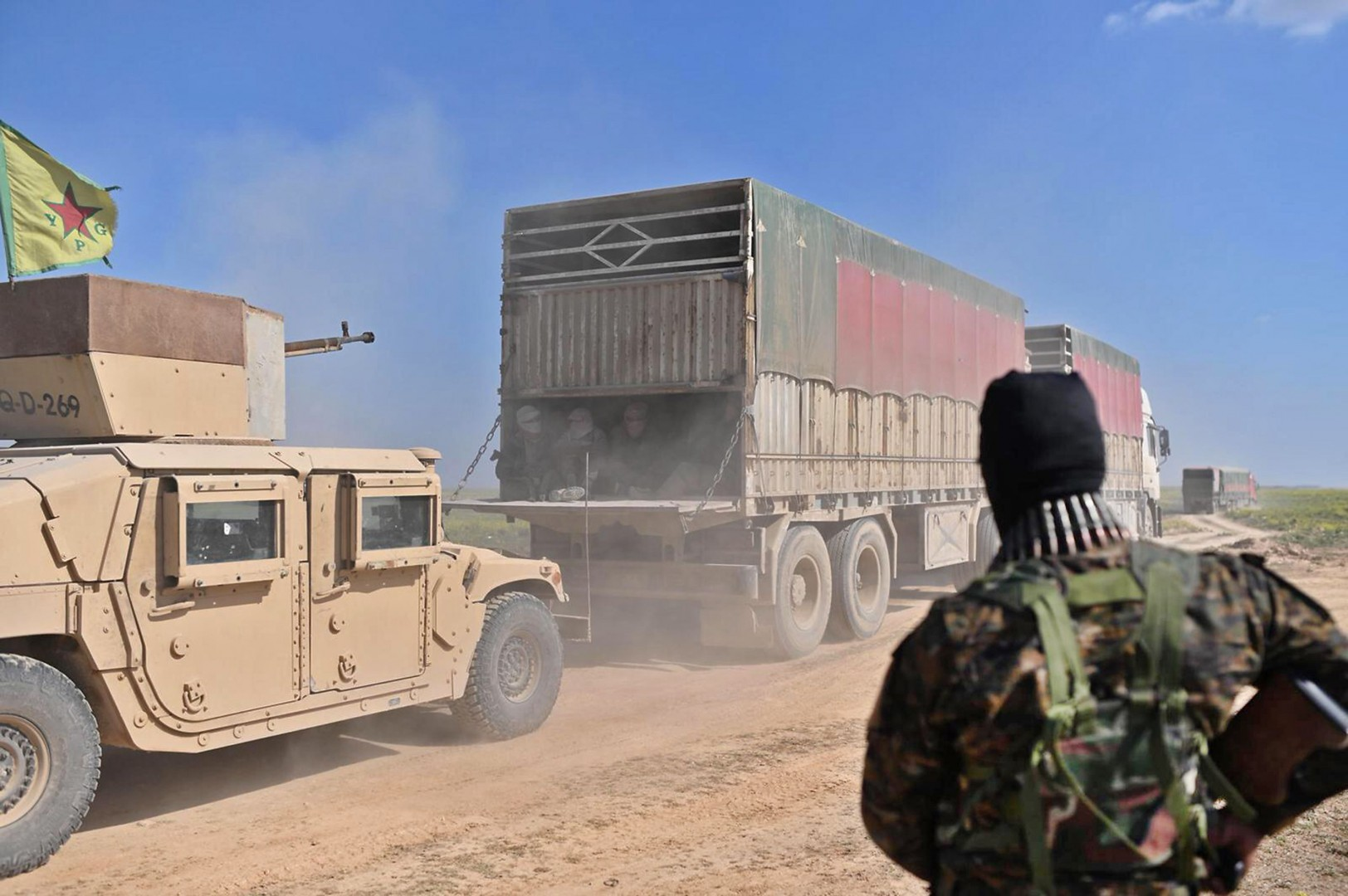 "A military vehicle with the US-backed coalition in Syria drives behind a convoy of trucks carrying Islamic State group's fighters and their families after they left IS's last holdout of Baghouz in Syria's northern Deir Ezzor province on February 20, 2019. - A convoy of trucks evacuated dozens of people from the Islamic State group's last Syria redoubt, bringing US-backed forces closer to retaking the final patch of their 2014 ""caliphate"". The implosion of the jihadist proto-state which once spanned swathes of Syria and neighbouring Iraq has left Western nations grappling with how to handle citizens who left to join IS. (Photo by Bulent KILIC / AFP)"