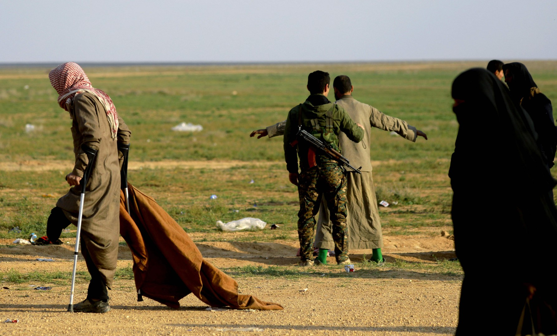 "a man suspected of being an Islamic State (IS) fighter is searched by a member of the Kurdish-led Syrian Democratic Forces (SDF) after leaving the IS group's last holdout of Baghouz, in Syria's northern Deir Ezzor province on February 22, 2019. - US-backed fighters trucked out civilians from the last speck of the Islamic State group's dying ""caliphate"" in Syria on February 22, eager to press on with the battle to crush the jihadists. More than four years after IS overran large parts of Syria and neighbouring Iraq, and declared a ""caliphate"", they have lost all of it but a tiny patch in the village of Baghouz near the Iraqi border. (Photo by Delil SOULEIMAN / AFP)"