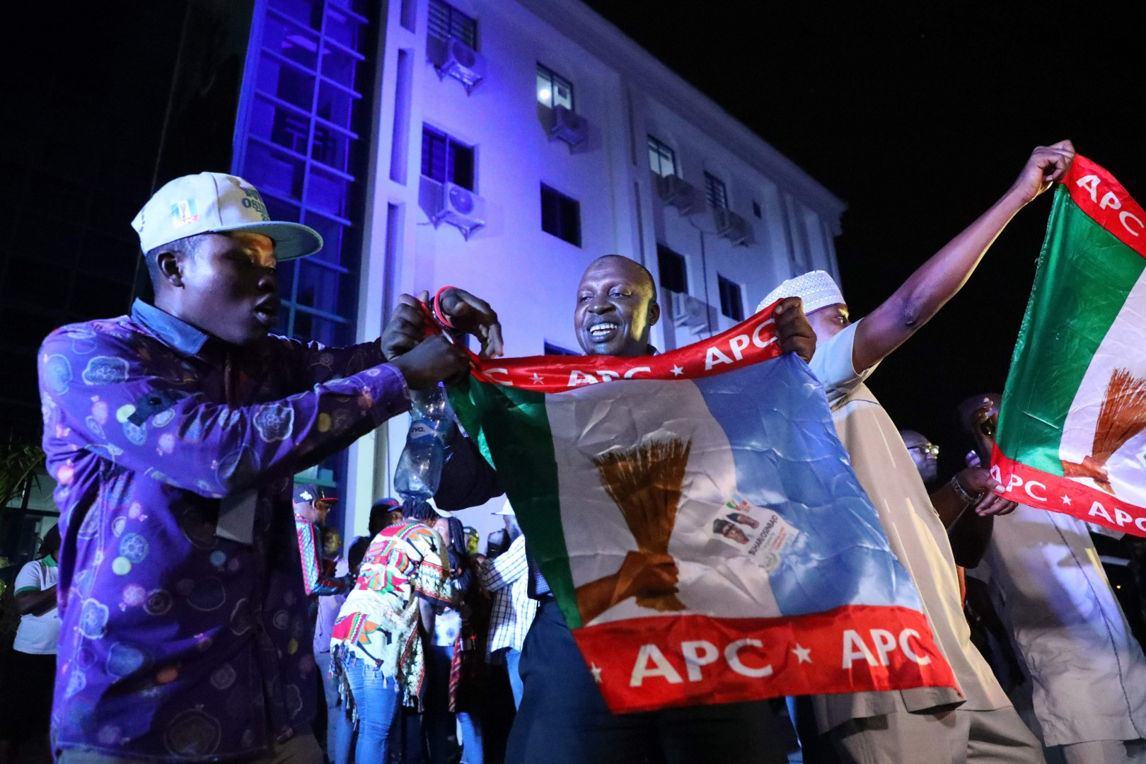 TOPSHOT - Supporters of the ruling All Progressives Congress (APC) celebrate with party flags in Abuja, Nigeria, after candidate President Mohammadu Buhari was re-elected on February 26, 2019. - Muhammadu Buhari was re-elected Nigeria's president, results showed February 26, 2019, after a delayed poll that angered voters and led to claims of rigging and collusion. Buhari, 76, took an unassailable lead of more than four million votes as the last states were yet to be declared, making it impossible for his nearest rival, Atiku Abubakar, to win. The win was confirmed as Abubakar won in the very last state to declare -- Rivers in the south -- but could not claw back the deficit. (Photo by KOLA SULAIMON / AFP)