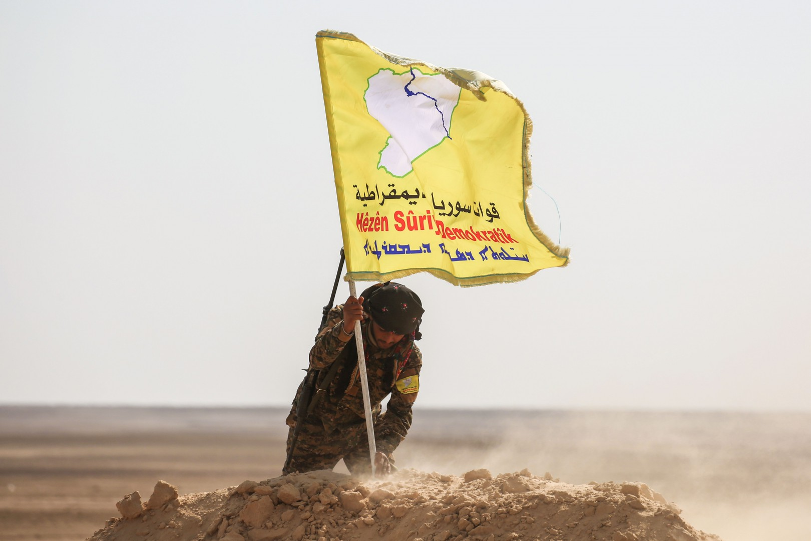 (FILES) In this file photo taken on February 8, 2017, a member of the Syrian Democratic Forces (SDF), made up of US-backed Kurdish and Arab fighters, raises a flag of the SDF near the village of Bir Fawaz, 20 kilometres north of Raqa during their offensive to retake the former the Islamic State (IS) group's stronghold in Syria. - Syria's Kurdish minority, hailed as an indispensable Western ally during the war against the Islamic State group, faces hard bargaining with Damascus now that Washington is winding down its campaign. (Photo by DELIL SOULEIMAN / AFP)