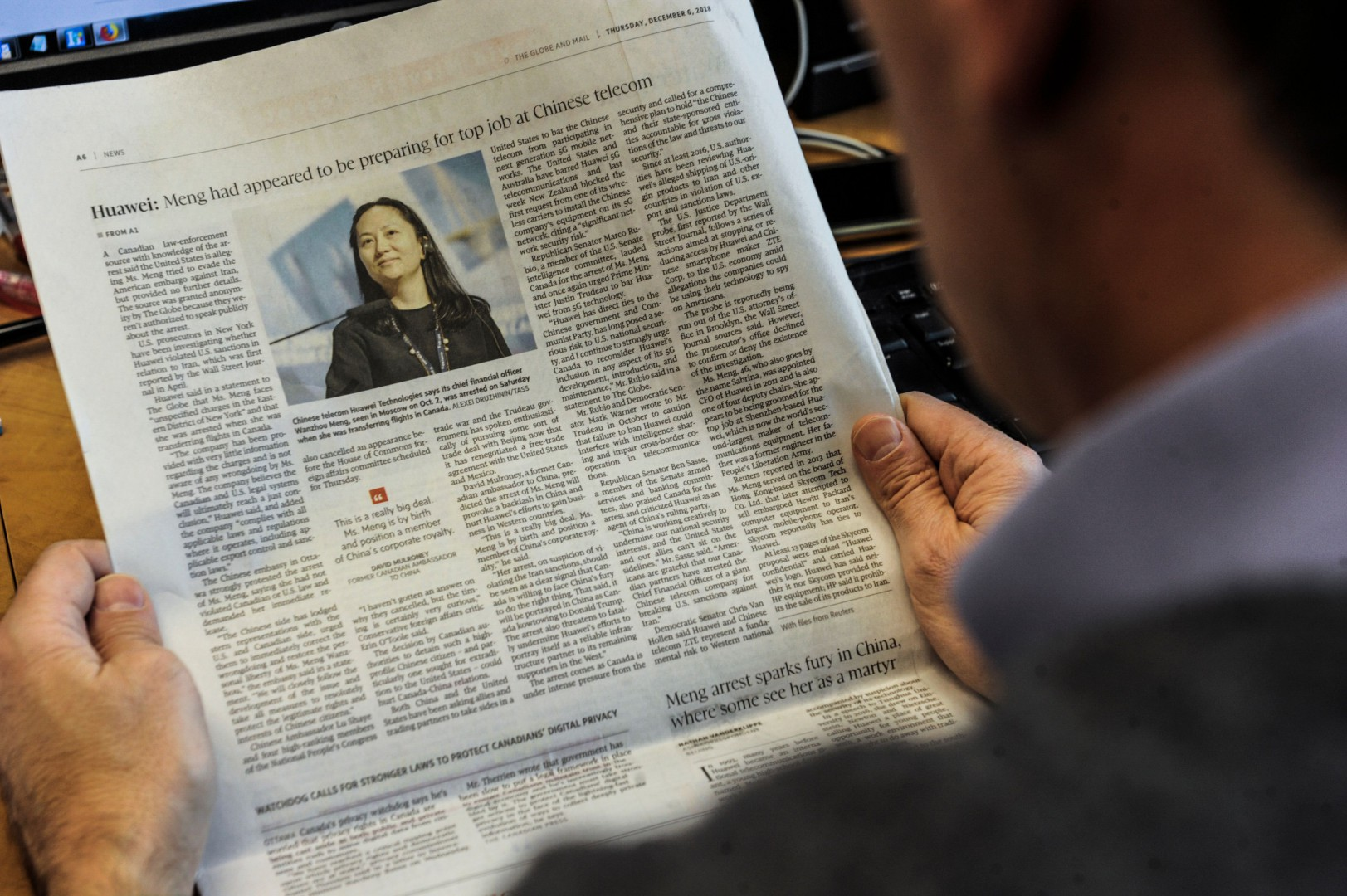An illustration shows a journalist reading a news page about tech giant Huawei in The Globe and Mail in Montreal, Canada, December 6, 2018. - The arrest of a top executive of Huawei at the request of US authorities signals a toughening stand in Washington on dealing with Chinese tech firms amid longstanding concerns over cyberespionage. Meng Wanzhou (pictured on the news page), Huawei's chief financial officer, was detained this week in Canada and faces an extradition request from US authorities over an investigation into suspected Iran sanctions violations by the Chinese technology giant. (Photo by Clement SABOURIN / AFP) / RESTRICTED TO EDITORIAL USE