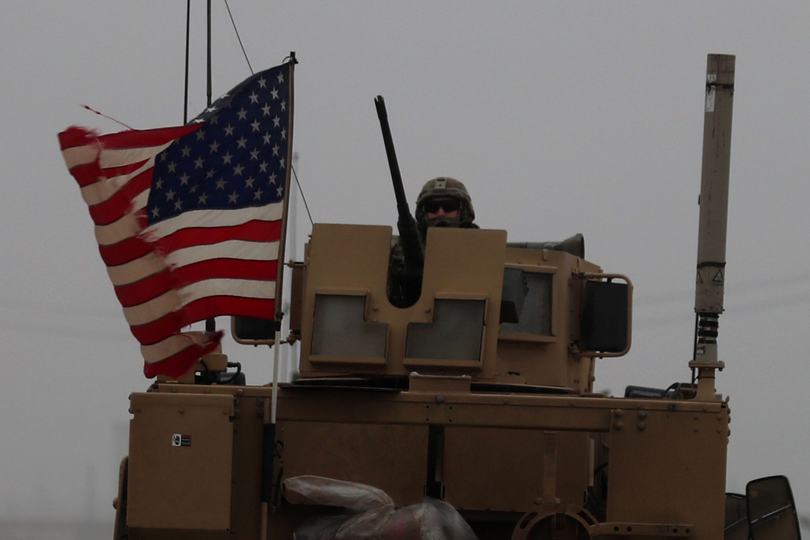 A picture taken on December 30, 2018, shows a US soldier riding an armoured personnel carrier as a line of US military vehicles patrol in Syria's northern city of Manbij. - President Donald Trump announced last week that US troops would depart from Syria, leaving Manbij residents dreading a long-threatened attack by Turkey. (Photo by Delil SOULEIMAN / AFP)